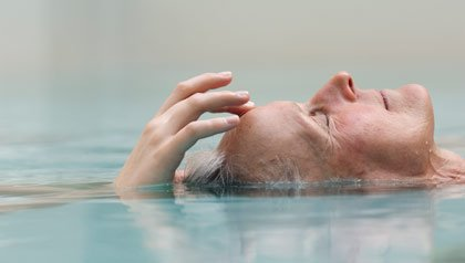 A woman meditates in a pool.