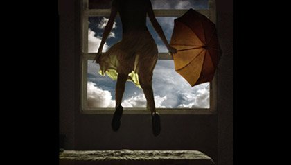 girl jumping inside on bed with umbrella