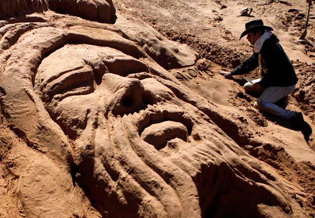 Un hombre trabaja en una escultura de arena que representa a Jesucristo durante la Semana Santa en Arenal de Cochiraya, Oruro, Bolivia - Pascua y Semana Santa