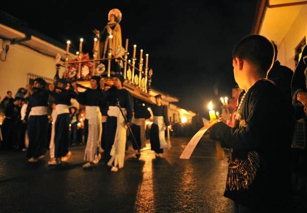 Penitentes caminan con la estatua de