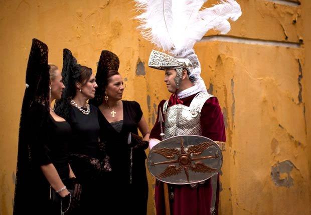 Las mujeres que usan la mantilla tradicional se ven al lado de un hombre vestido de romano en la puerta de entrada de la iglesia La Macarena  antes de participar en una procesión durante la Semana Santa de Sevilla, al sur de España - Pascua y Semana Santa