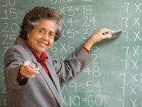 Mujer mayor en frente de un tablero de colegio