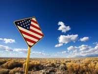 Persiguiendo el sueño americano – Letrero en la carretera con la bandera de Estados Unidos.