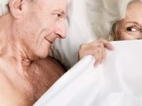 Better sex in the new year- a senior couple flirt in bed