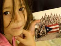 """Pebbles I. Ferrer Barber, de 5 años, muestra una foto del """"pelotón perdido"""" al que perteneció su padre."""