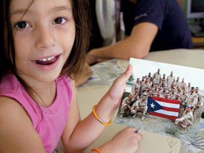 girl holding photo of soldiers in Iraq