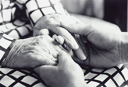 Hombre acariciando las manos de una anciana