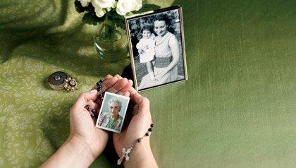 Manos sosteniendo foto de papá con un rosario entrelazado y otro retrato al lado