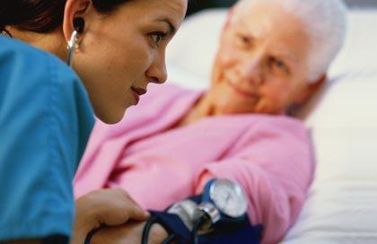 Enfermera cuidando a una mujer mayor en su hogar