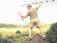 Hombre en el techo de su casa con una antena de televisión - Hay aspectos legales en ayudar a un amigo o vecinos.