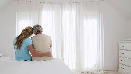 Mama e hija sentadas en una cama - Cómo obtener ayuda financiera para cuidar a sus padres