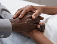 Man holding older woman's hands-the high price of family caregiving