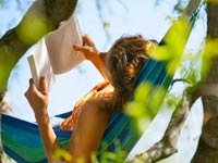 Mujer leyendo en una hamaca al aire libre