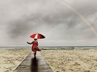 Mujer caminando hacia el mar en un día con un arco iris
