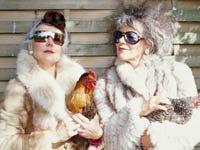 Un par de mujeres mayores posando con unas gallinas.