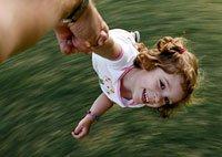 Hombre mayor juega a darle vueltas a una niña en el patio de su casa