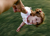 A mature man swirls a three-year-old girl around in the backyard.
