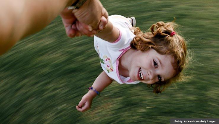 A mature man swirls a three-year-old girl around in the backyard.
