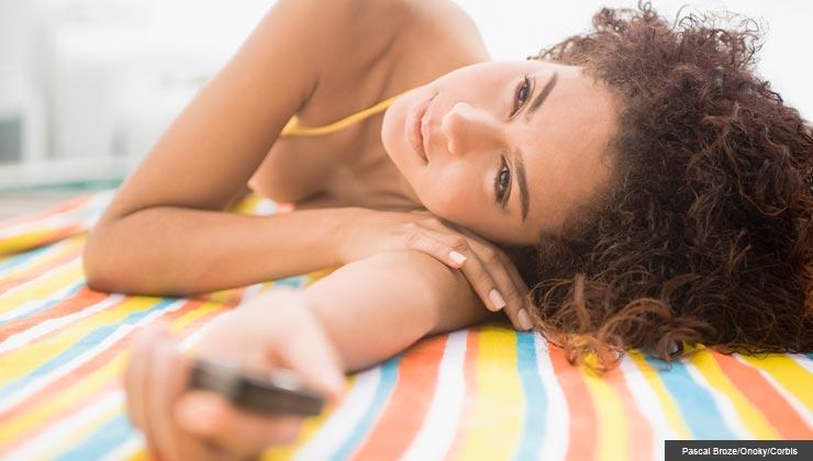Young woman lying poolside.