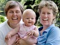 Happy lesbian couple with baby daughter for financial planning for LGBT 50+
