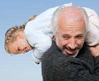 Senior man crarrying granddaughter on his shoulders