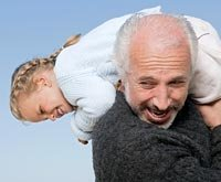 Senior man crarrying granddaughter on his shoulders