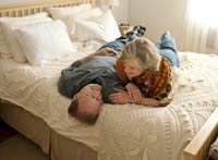 Ageless Love-AARP-Michael Downs, wife Sheri Venema smile on bed at home.