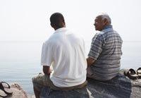 Padre e hijo en las rocas por el agua, cómo ayudar a los hijos adultos desempleados