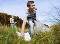 Un joven limpia basura en los alrededores; los jóvenes son más enfáticos e idealistas de lo que las generaciones mayores temen.