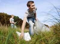Young adults are more empathic and idealistic than older generations fear- a young man cleans up trash in the outdoors