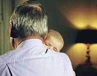Grandfathers can often be better grandparents than they were fathers according to this essay published on AARP.org- a grandfather snuggles his baby grandchild