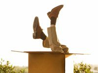 man upside down and sticking out of large box - Jaquelyn Mitchard's intelligent gift giving guide for the more mature