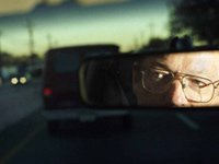 Reflection of senior man in car mirror - how to take car keys away from senior drivers