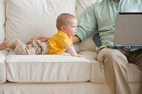 Padre trabaja en su computador portátil con su hijo sentado en el sofa de la casa - La historia de su familia esta tan sólo a un clic