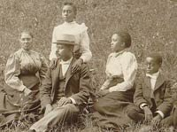 African American family posed for portrait seated on lawn, 1899