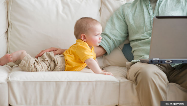 father sits with laptop and son on sofa
