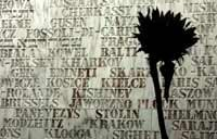 A schoolchild holds a sunflower in front of the wall of remembrance at the Museum of Tolerance in Los Angeles, CA.