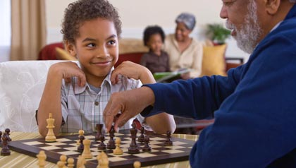 family activities during the christmas season- a grandfather plays chess with his grandson