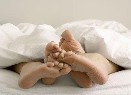 Pies de una pareja en la cama