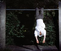 Man hanging upside down on a monkey bar in a playground.