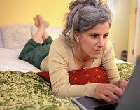 Mujer en su cama con su computador portátil - 8 Formas de buscar su amor en línea