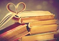 best books about romance- a stack of books with a heart folded in the pages