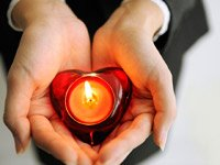 hands holding candle in heart-shaped candle holder