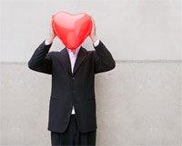 Hombre tapándose la cara con un globo en forma de corazón