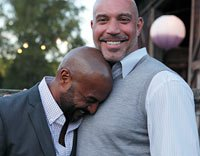Male couple outdoors laughing, candid