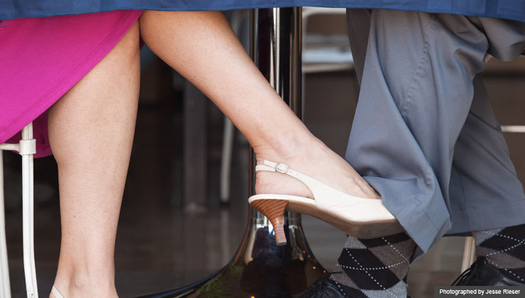 Couple playing footsie underneath cafe table