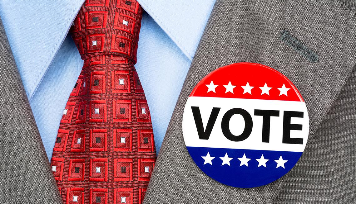 Un hombre lleva un botón de las elecciones en la solapa de su traje.
