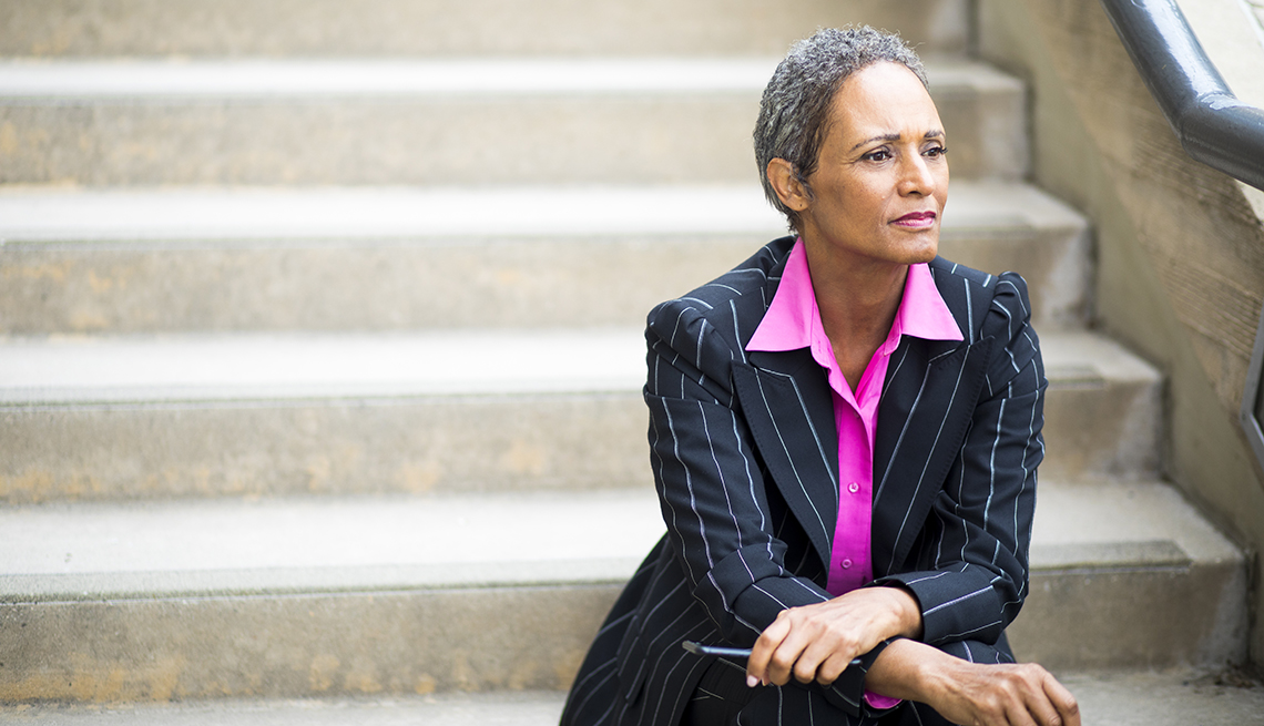Female in business suit sitting on stairs