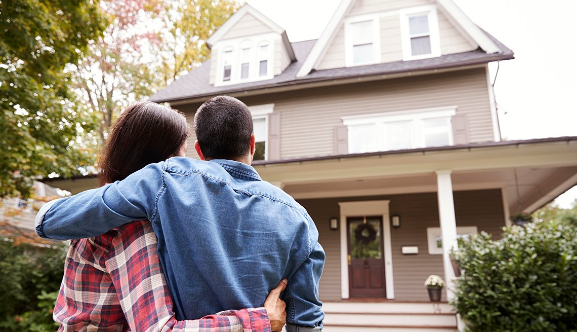 Rear view Of loving couple looking at a house
