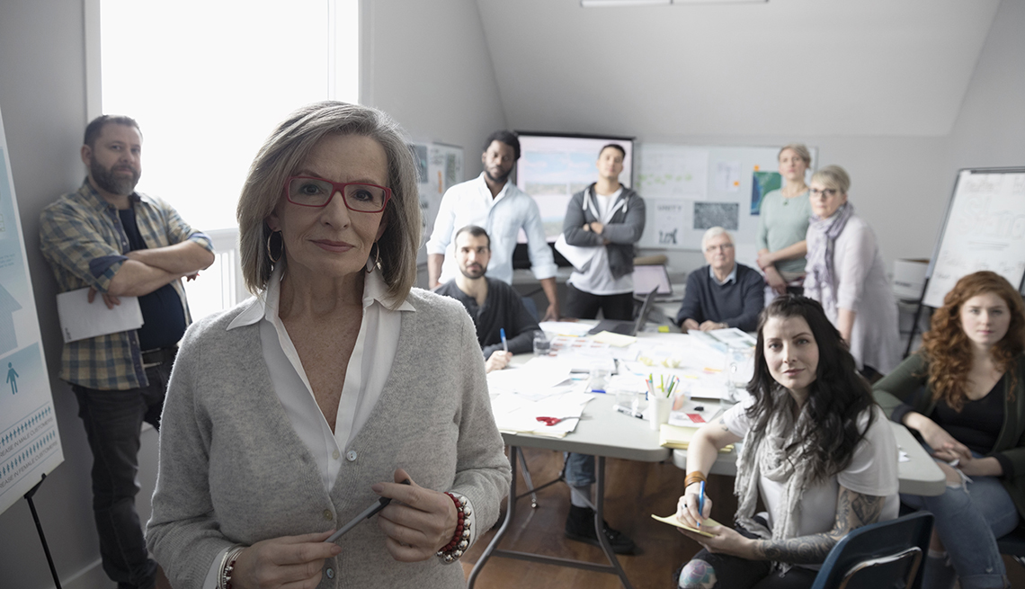 Portrait confident woman and volunteers working in office